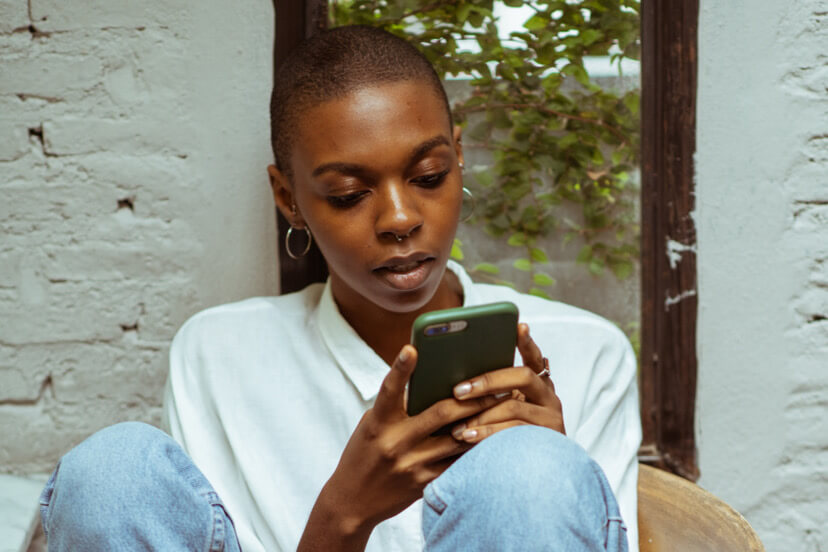 an african woman texting on a phone